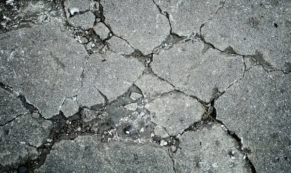 Close up picture of a concrete driveway that is cracked and needs repaired for a customer of pro concrete contractor