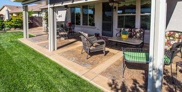 Picture of a stamped concrete patio in the backyard of a newly renovated home by pro concrete contractor