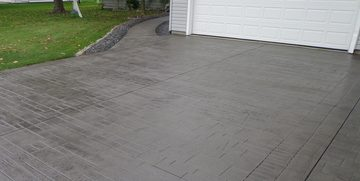 Picture of a new stamped concrete driveway include sidewalk on the side of the house by pro concrete contractor
