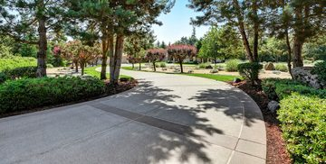Picture of a long concrete driveway poured in front of a luxury home with perfect landscaping by pro concrete contractor