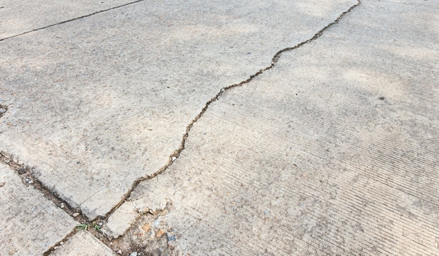 Closeup picture of a cracked concrete driveway in Cleveland, OH