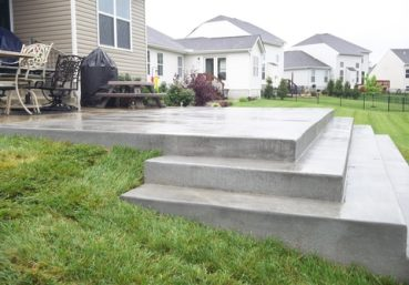 Picture of a concrete patio and steps going down a hill in the backyard of a customer in Clarksville, TN.