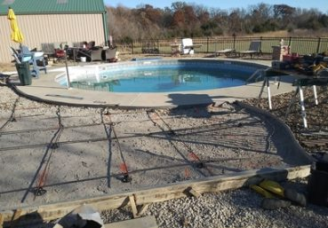 Picture of a new swimming pool installed with a concrete patio poured around in it in Tallahassee, FL
